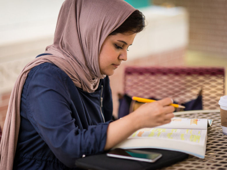 A female student studies a highlighted textbook.