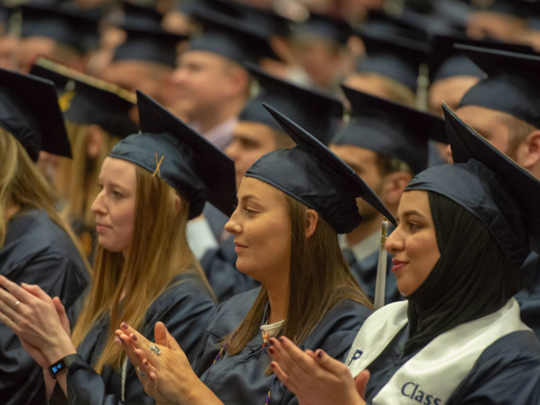 Three female Penn State Behrend graduates participate in commencement.