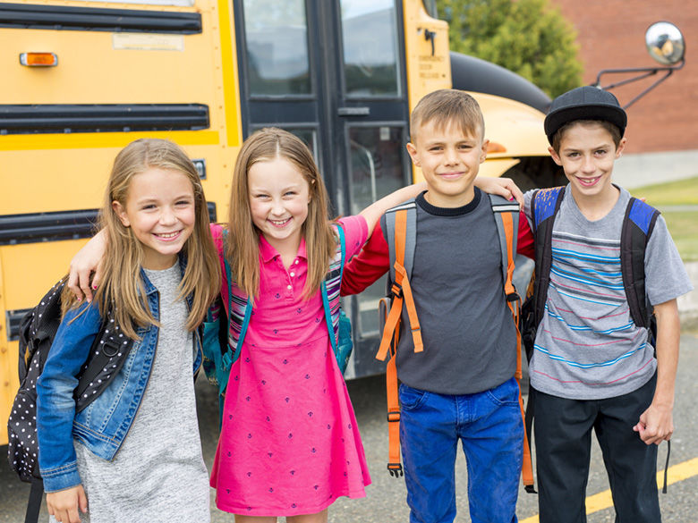 Middle-School Students in front of school bus © Can Stock Photo  Lopolo