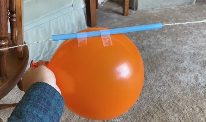 Inflated balloon taped to straw on string