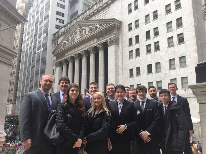 A group of Black School of Business students stand in front of the New York Stock Exchange.