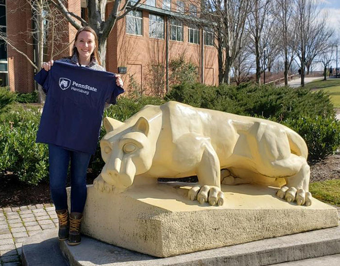 Kailee Shotto stands next to the Harrisburg Lion Shrine and holds up a Penn State Harrisburg tee shirt.