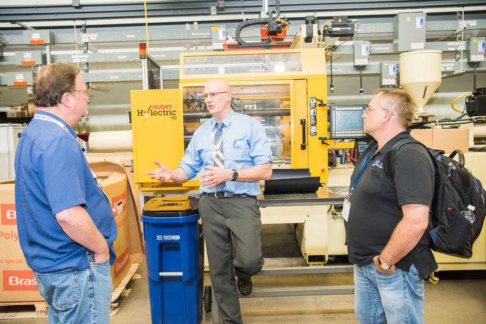 Brian Young, an associate professor of engineering, instructs two students during a Plastics Training Academy course.