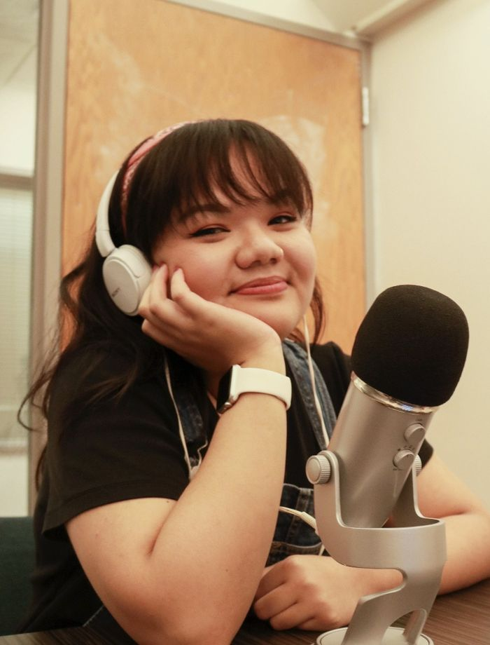 Victoria Pham sits with her chin resting in her hand, wearing a headset and sitting in front of a microphone.