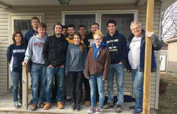 Student-athletes at a Habitat for Humanity build. Students are flanked by athletics staff members Gabi Quiggle, administrative support assistant, and Brian Streeter, senior director of athletics.
