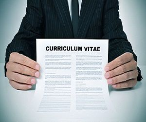 Image of a person in a suit holding a paper labeled Curriculum Vitae