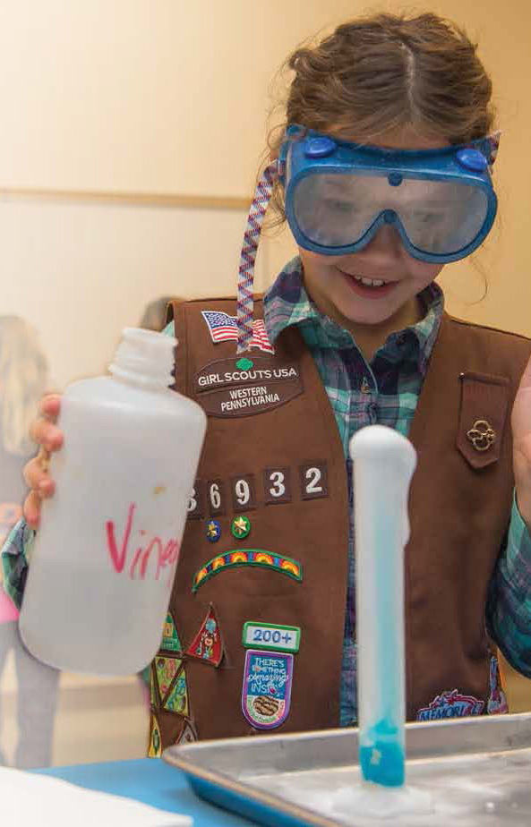 A Girl Scout works on an experiment on Behrend's Youth Education Outreach Scout day.