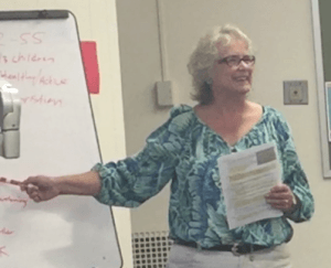 Mary Baird walks a group of mentors-in-training through an assumptions activity at Mercyhurst University.
