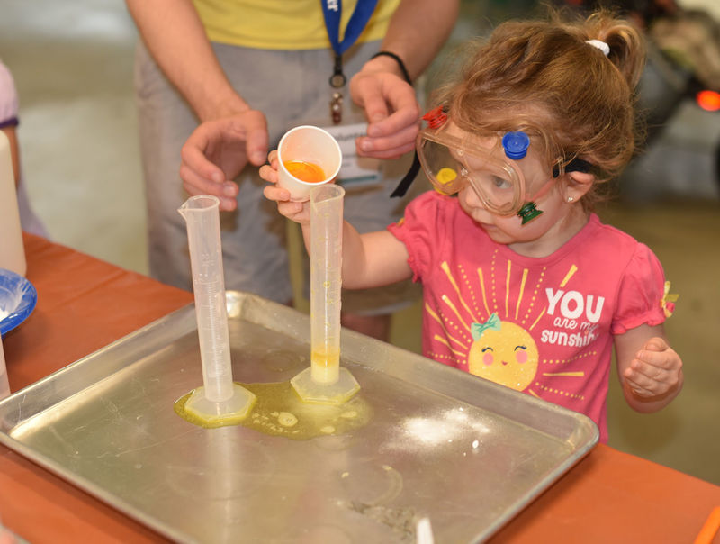 A preschooler works on a science experiment during Preschool Science Story Time.