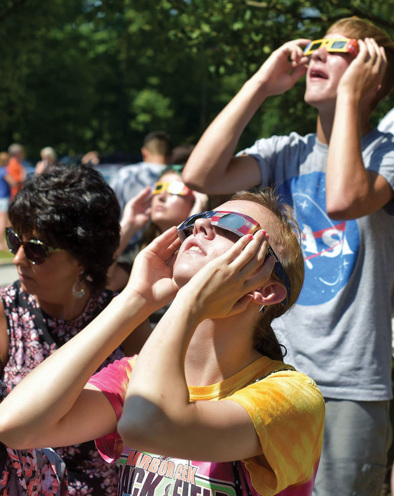 People watch the solar eclipse with safety glasses