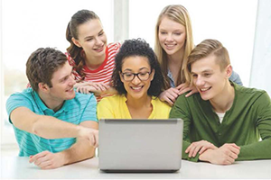 Five students looking at a computer