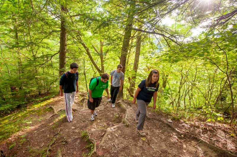 Students walk through a wooded area of Wintergreen Gorge near the Penn State Behrend campus.