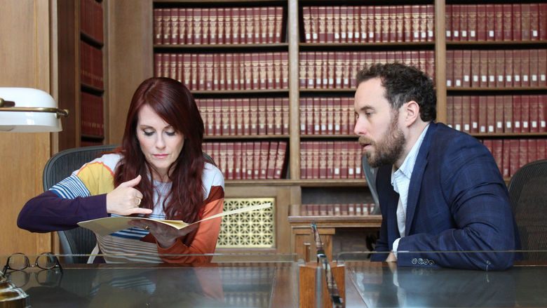 Two people talk at a researcher's table at the National Archives in Washington, D.C.
