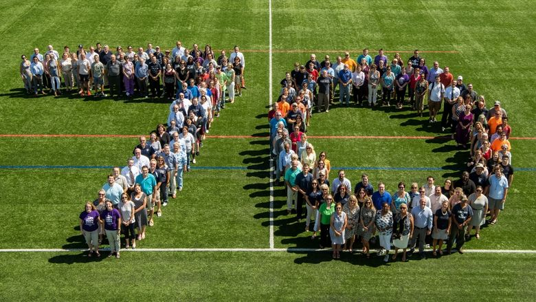 Faculty, staff and students assemble on a Penn State Behrend field in the formation of a 70.