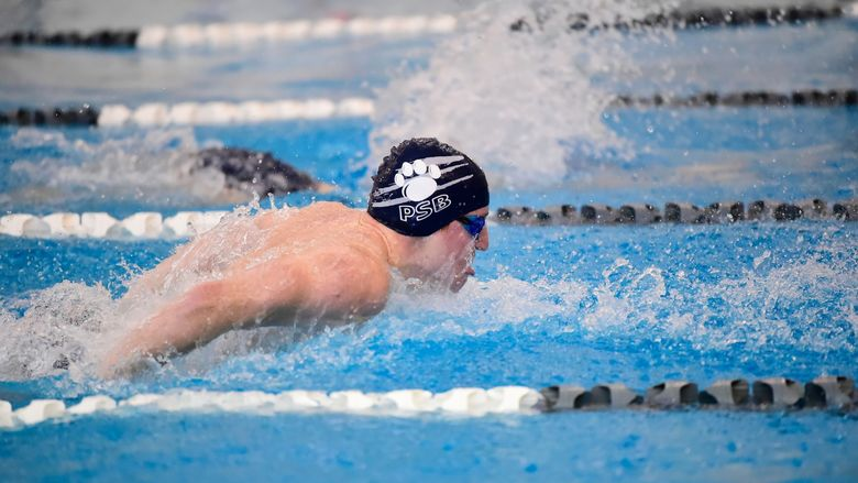 A Penn State Behrend male swimmer competes in a race.