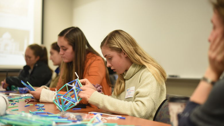 Victoria Purchase works to create a dome during Women in Engineering Day at Penn State Behrend.