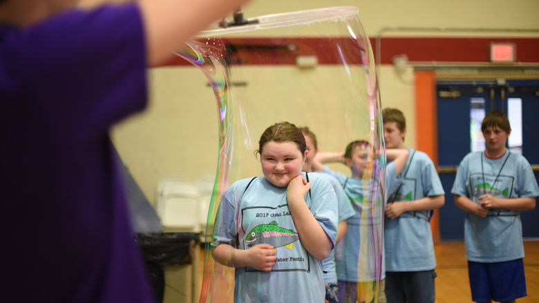 A fifth-grade student enters a life-size bubble.