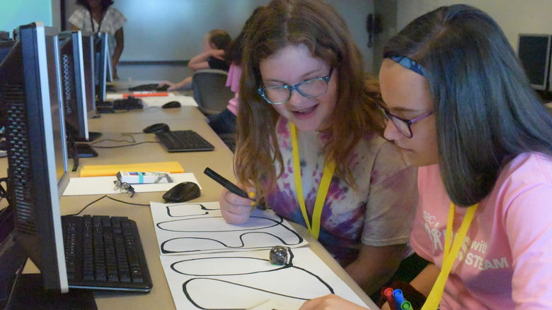 Emma Stafford, left, and Kendra Kope, both students in the General McLane School District, program an Ozobot during the Wabtec Girls With Steam program.