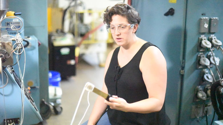 Cleveland-based sculptor Lauren Herzak-Bauman manipulates plastic while working in Penn State Behrend's plastics processing lab.