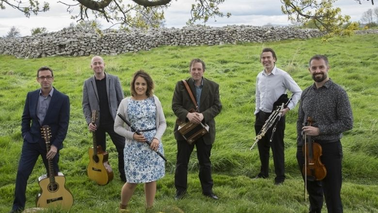 The musicians from the Celtic band Danu pose in a green field.