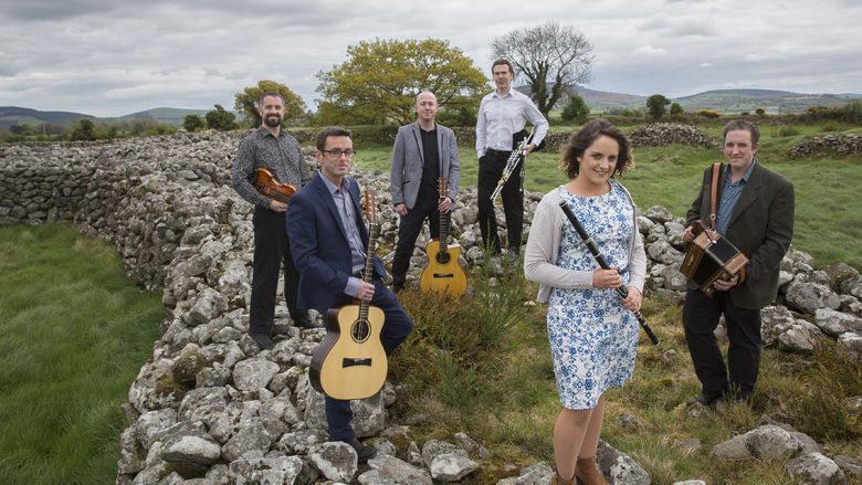 The musicians in the band Danu pose on rocks in a country field.