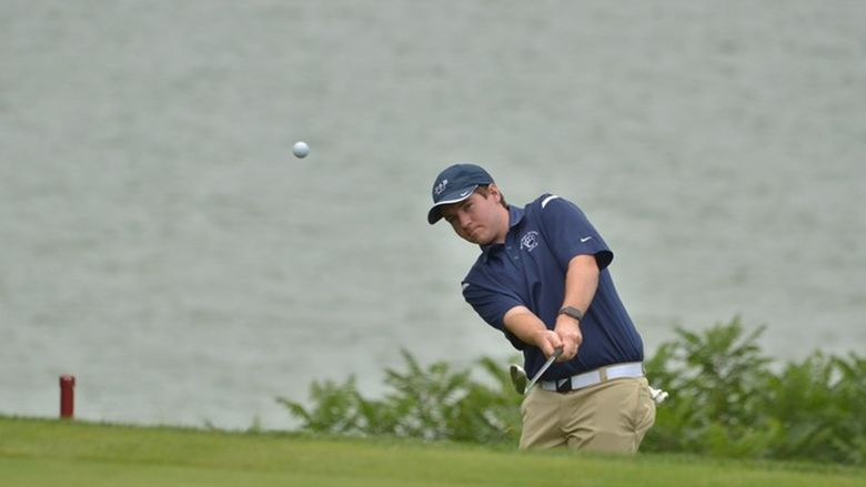 A Penn State Behrend golfer chips the ball onto the green.