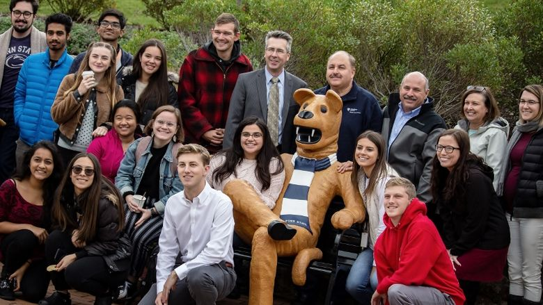 Students, faculty and staff pose at Penn State Behrend's new Lion bench.