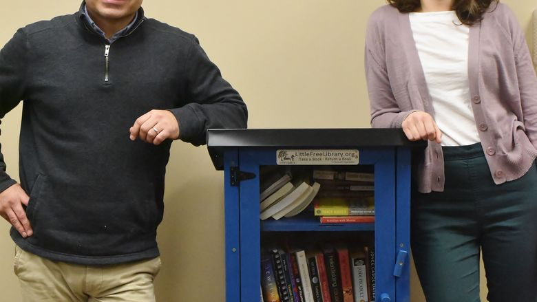 "Two Penn State Behrend staff members stand next to one of the college's ""Free Little Libraries"""
