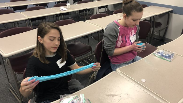 "Danica Park, left, and Kristine Wurst play with the slime they created during ""The Science of Slime"" workshop at Penn State Behrend's Math Options Career Day."