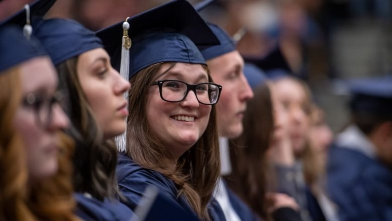 A Penn State Behrend graduate smiles during the college's commencement ceremony.