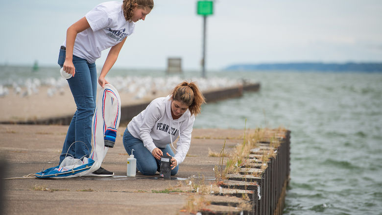 Two female students check a net after sampling Lake Erie for bloody red shrimp.