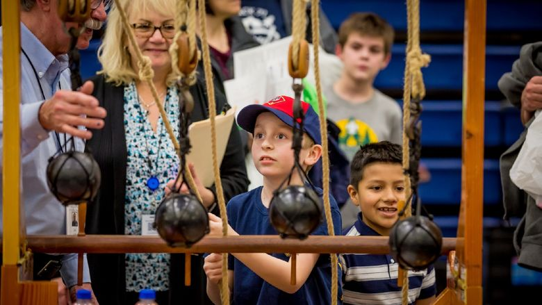 A child tests a pulley system at Penn State Behrend's STEAM fair.