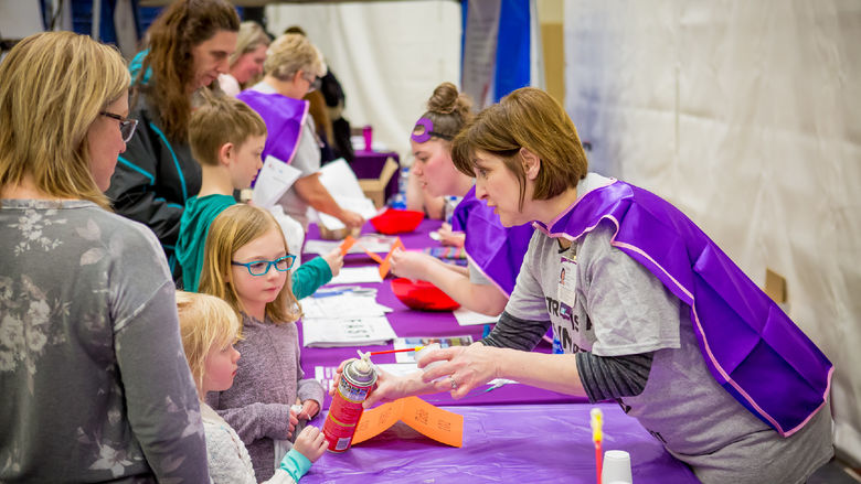 A volunteer teaches children and their parents how to recognize the symptoms of a stroke.