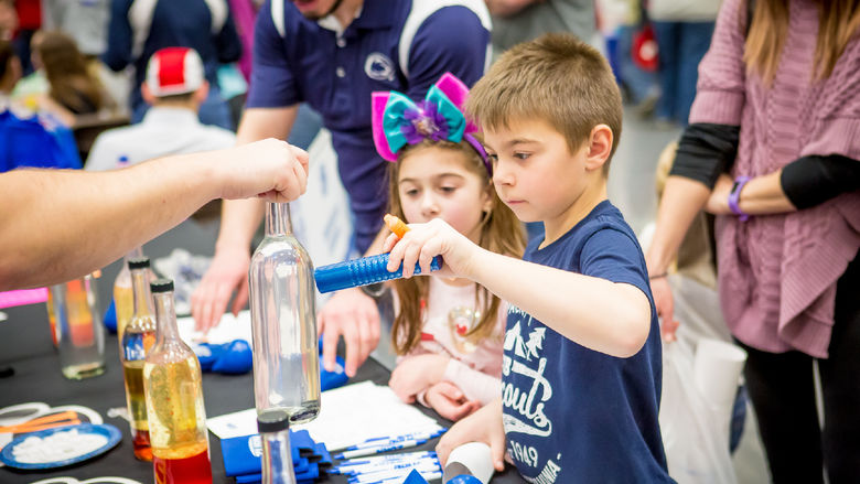 Children experiment with magnets and glass at the Penn State Behrend STEAM fair.