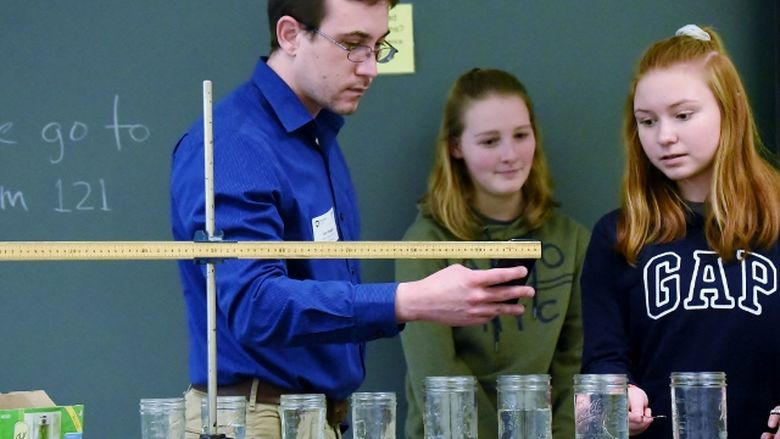 Two students and an instructor record the pitch of a struck water glass at the 2019 regional Science Olympiad at Penn State Behrend.