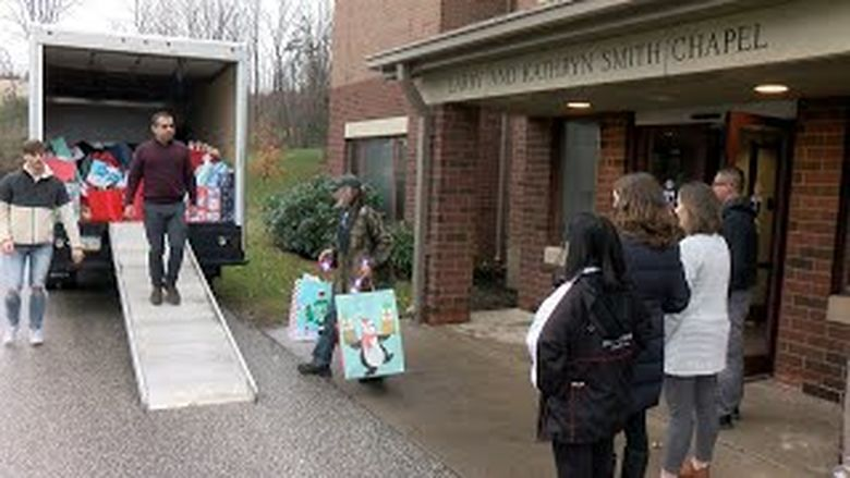Volunteers load holiday gift bags into a truck.