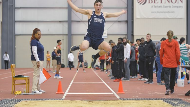 A Penn State Behrend athlete competes in the long jump at an indoor meet.