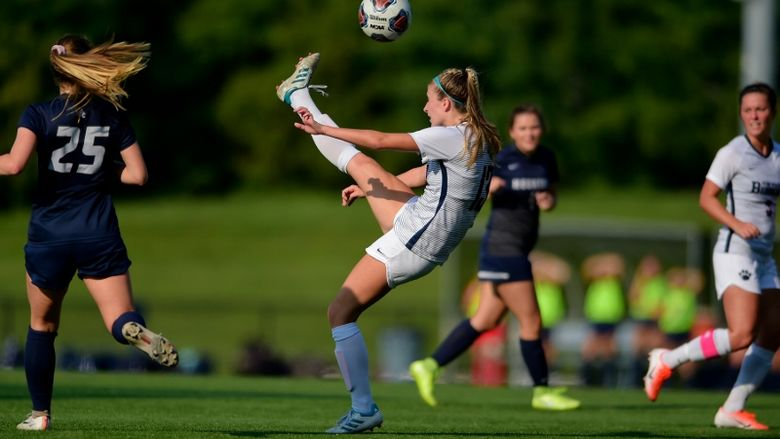 A Penn State Behrend soccer player kicks the ball over her head.