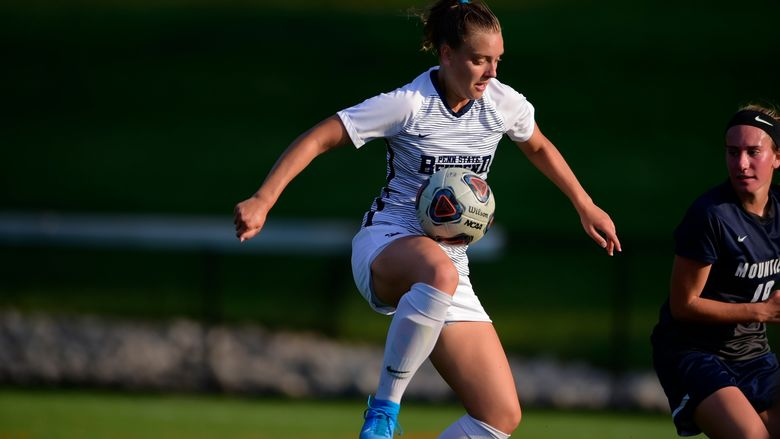 A female Penn State Behrend soccer player juggles the ball off her knee during a game.
