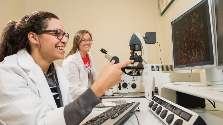 Two students work on the confocal microscope at Penn State Behrend