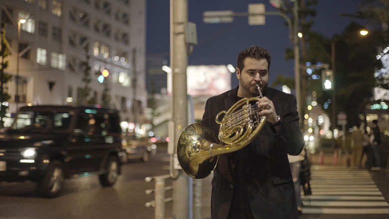 A french horn player holds his instrument while walking in the street.