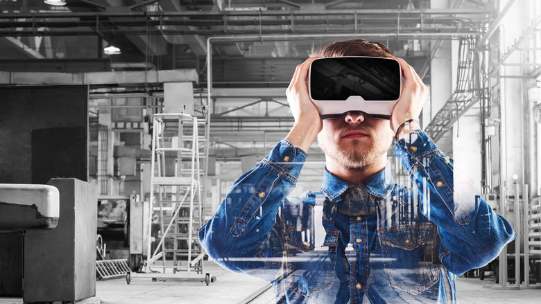 A man in an industrial setting looks through a virtual-reality headset.