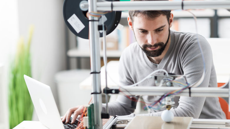 A man works with a 3D printer.