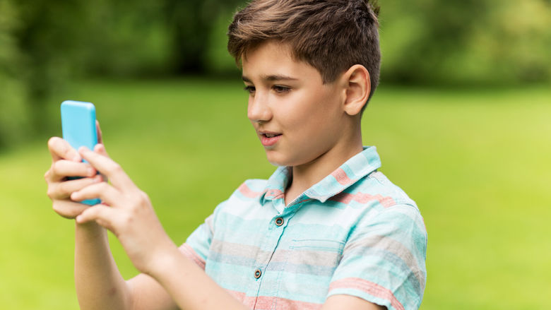A boy holds a smartphone while completing a virtual scavenger hunt.