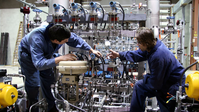 Two employees work in an advanced manufacturing setting.