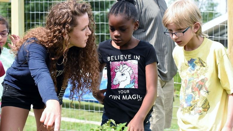 Penn State Behrend student Celeste Makay gives two younger students a tour of the campus garden.