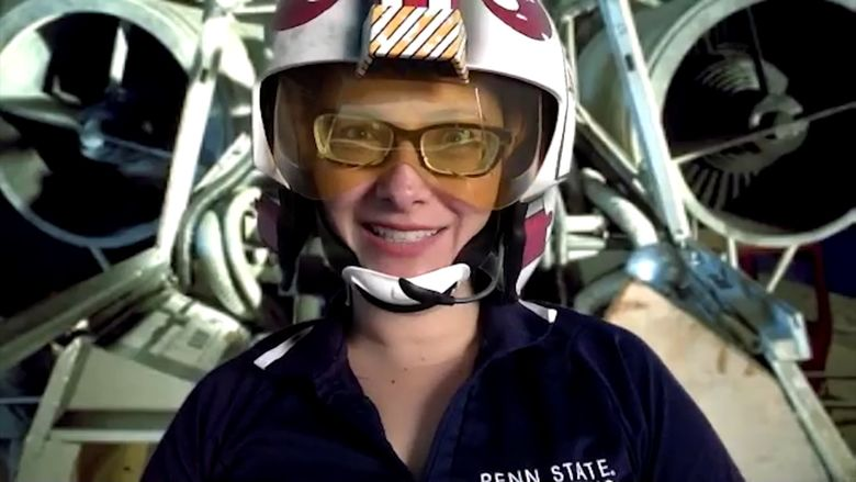 "Penn State Behrend professor Charlotte de Vries wears a prop helmet while teaching in front of a screen showing an image from ""Star Wars""."