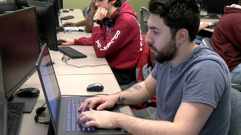 Male student works at a laptop computer.