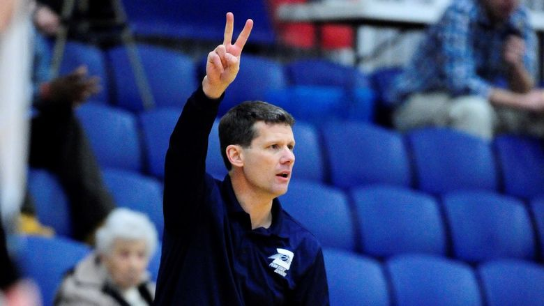 Penn State Behrend men's basketball coach Dave Niland signals to his team from the sideline.