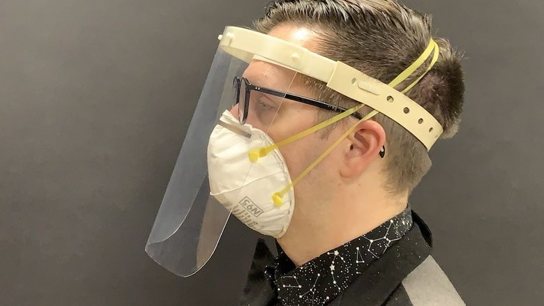 A product developer models a medical face shield for use in COVID-19 environments.